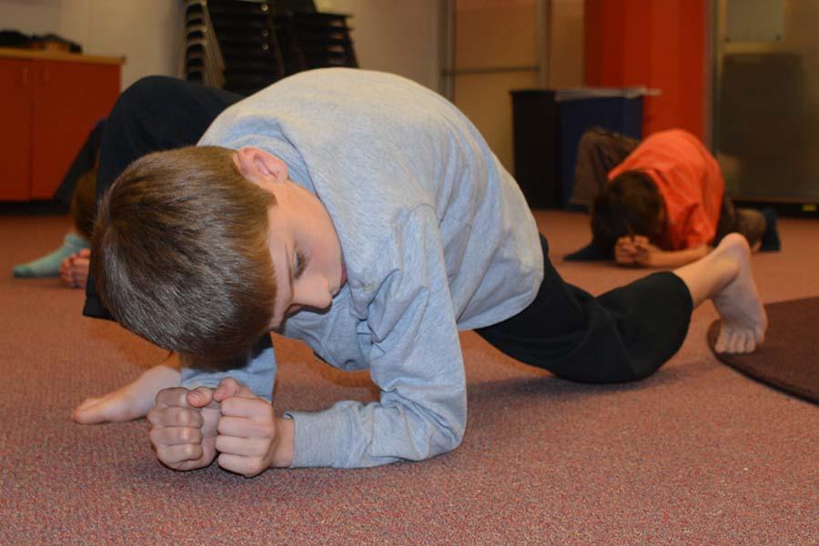 Capoeira-children focus during beginning stretches