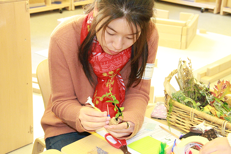 Workshop participant affixing leaves and toothpicks to a cork