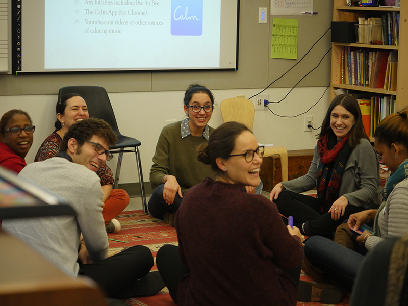 Workshop participants sitting in a circle and laughing